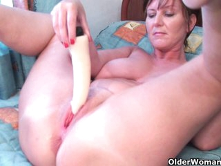 Granny Joy plays with her dildo collection